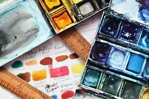 A watercolour paint palette with vintage rulers on top of an artists sketchbook