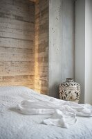 Double bed with white bedspread and urn against exposed concrete wall
