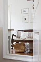 Wicker bag and rustic wooden bench with seat cushions reflected in mirror