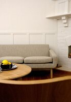 Couch with beige upholstery and round coffee table next to whitewashed brick wall