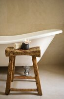 Free-standing, antique bathtub and rustic stool