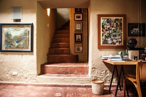 Office with narrow staircase and collection of photographs above desk against rustic wall