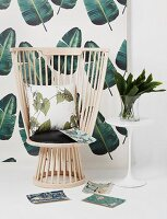 Designer reading chair with cushions against jungle-patterned wallpaper