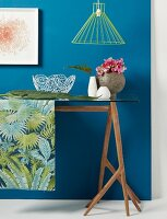 Still-life arrangement on jungle-patterned runner on glass table against blue wall