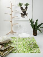 Delicate white metal chair on jungle-patterned rug, stacked cushions on floor and artistic, tree-shaped coat rack in untreated wood in background