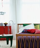 Schlafzimmer mit Holzbett, Dekokissen & Nachttischchen auf Flokati