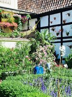 Half-timbered house with veranda & summery garden