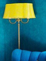 Antike gelbe Stehlampe vor blauer Wohnzimmerwand