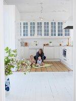 Mutter mit Kindern in weisser Küche im skandinavischen Stil