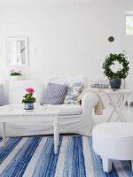 Wohnzimmer in schwedischem Stil mit weißem Sofa & blau-weißem Teppich