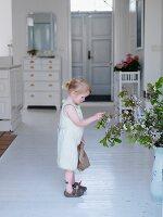 Kleines Mädchen betrachtet Blumenstrauss im Hausflur
