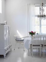 White interior with dining table, chandelier, cot & dresser