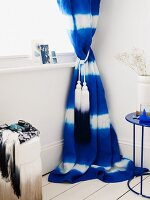 Blue and white curtain with tassels in corner of room