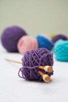 Several balls of wool with knitting needles through one ball