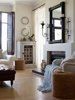 Mirror and candle sconces above open fireplace and vintage wine cabinet in living room with wooden floor