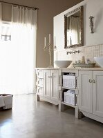 Candlestick on country-house-style bathroom units and framed mirror above washbasin
