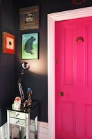 Shiny table lamp illuminating collection of pictures on dark grey wall next to hot pink panelled door