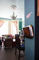 View into room with bay window, upholstered furniture and flea-market magazine rack on blue-painted wall pillar