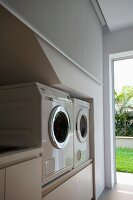 Utility room with elevated washer and dryer next to open door with view of sunny garden