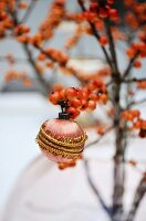 A vintage christmas bauble hanging from a branch of winter berries in a vase