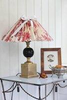 Table lamp with hand-crafted lampshade in red and white toile de jouy fabric on metal table against white, wood-clad wall