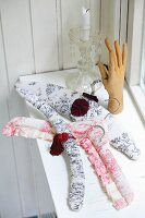 Coat hangers with handmade covers in toile de jouy fabric and sculpture of hand in front of candlestick on windowsill