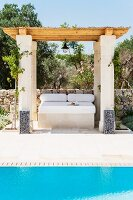 Daybed with white cushions below shady, wooden pergola on stone pillars behind pool in Mediterranean garden