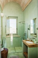 Green-painted bathroom with vaulted ceiling, masonry washstand with wooden surface and floor-level shower with glass partition below window