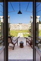 View through open terrace door of antique chairs on stone floor in front of sunny, Mediterranean garden
