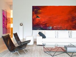 Easy chairs with metal frames and black covers in front of glass coffee table and white sofa below red modern artwork on wall