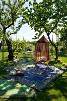 Sunny garden with patterned rugs on lawn and airy canopy hanging from tree