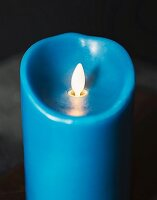 single blue candle in a dark setting
