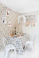 Dining area set for Easter in kitchen decorated with hen motif on wallpaper and tablecloth and white, vintage chairs