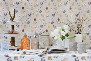 Napkins, tablecloth and wallpaper with colourful hen pattern and grey crockery with hen-motif relief on table set for Easter