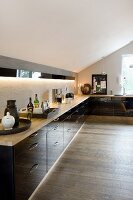 Black, glossy, fitted corner kitchen in attic apartment with country-house board floor
