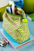 Fabric cosmetics bag with pattern of apples and apple tag on zip