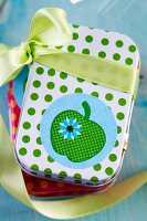 Small tin with green polka-dots decorated with apple sticker and ribbon