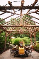 Outdoor Al Fresco dining setting with grape vine ball chandelier and wood pergola