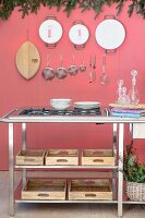 Gas hob on metal-framed counter above wooden boxes on shelves in front of kitchen utensils hung on pink wall