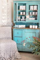 Packages of scented candles in turquoise dresser next to chair with loose cover