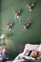 Antlers and fairy lights on green bedroom wall
