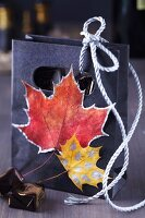 Small gift bag decorated with painted autumn leaves