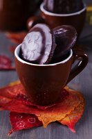 Autumn leaves used as coaster for espresso cup filled with biscuits