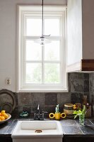 Vintage sink surrounded by stone tiles below tall, white lattice window