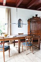 Long, rustic wooden table, wooden chairs, designer pendant lamps and antique wooden cupboard in renovated country house