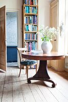 Bright reading room with tall bookcase and round wooden table decorated with white flowers in jug-shaped vase