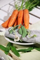Felt pea pods arranged on rolled linen napkin in front of bunch of carrots