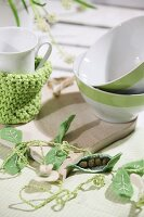 Spring arrangement with felt pea pods on table set with wooden boards, cereal bowls and crocheted teacup cosy