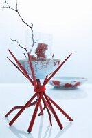 Oriental table decoration: Oriental bowl balanced on red chopsticks