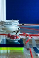 Oriental table setting: cutlery wrapped with red woollen yarn, fruit bowl on plexiglass blocks and stacked plates and dishes in background
